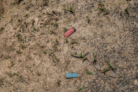 Used and empty shotgun shells from a rifle left and discarded laying on the dirt smashed and buried in the ground Stock Photo