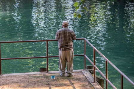 A man standing on the pier fishing at the lake with a fishing pole and a container of bait alongside him closeup on a sunny day in summertime