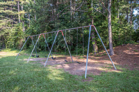 A worn and used swing set sits abandoned in the park a metal frame with chains holding the rubber seats and a dirt pad with the woodlands in the background on a sunny day in summertime