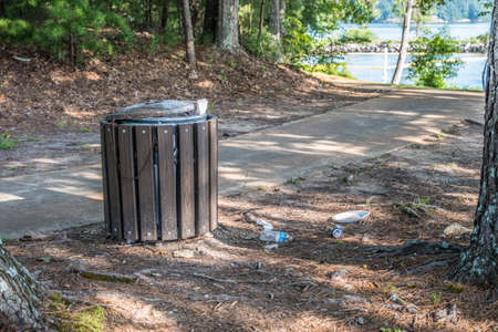 Several pieces of plastic paper and a aluminum can laying on the ground by a overflowing garbage can along the trail with the lake in the background