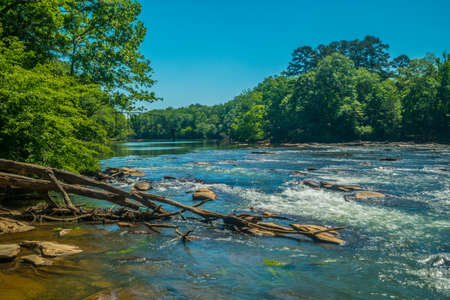 A view down the chattahoochee river with remains of an old iron bridge in the background on a bright sunny day in late spring