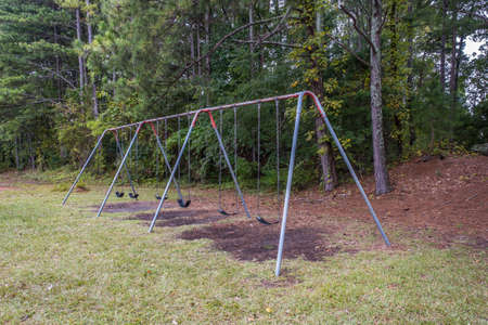 Angle view of an old empty metal swing set with rubber seats hanging by chains with the ground worn from swinging in a park on a cloudy day in early fall