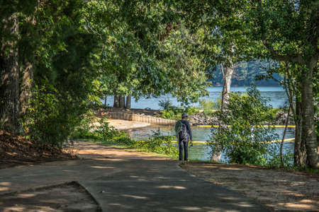 A man walking down the trail through the woodlands towards the beach area of the lake looking for a spot to go fishing while carrying his tackle on a bright sunny day in summertime