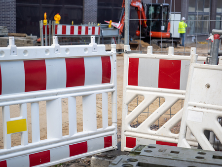A red white barrier of a construction site in the city