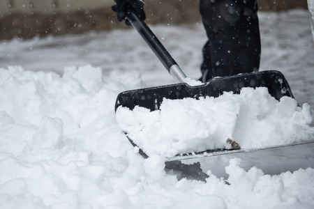 Someone is  shoveling snow outside in winter while it is snowing