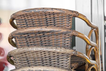Rattan chairs are stacked in front of a shop