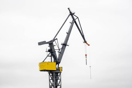 A crane works at the harbor in front of white sky