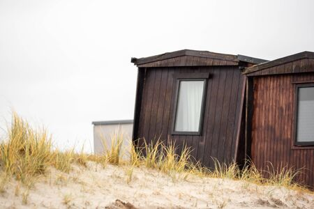 Old small huts as wood on a dune