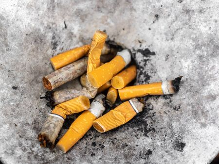 Squeezed remnants of cigarettes in an ashtray Stock Photo