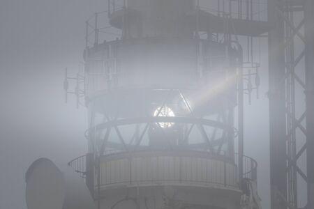 A lighthouse lights up on a foggy day Stock Photo