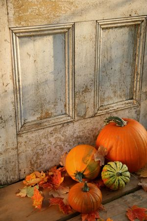 Pumpkins, broom and gourds at the door ready for halloween photo