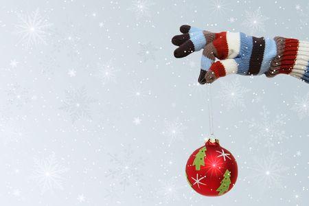 Winter mitten holding a Christmas ball photo