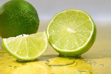 freshly: Freshly cut limes  with lime wedge with water droplets Stock Photo