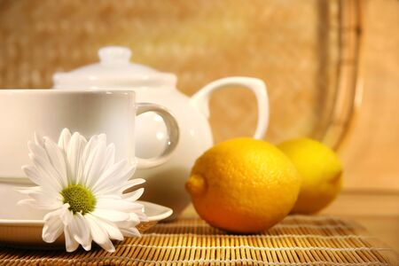 Tea cup  and teapot with lemons on the table