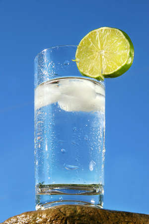 Cold glass of water with ice against a blue sky