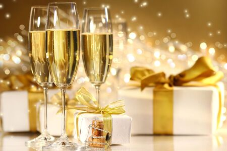 new year's day: Glasses of champagne with gold ribboned gifts
