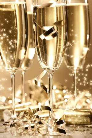Golden champagne sparkle with fluted glasses and party ribbons Stock Photo - 2522486