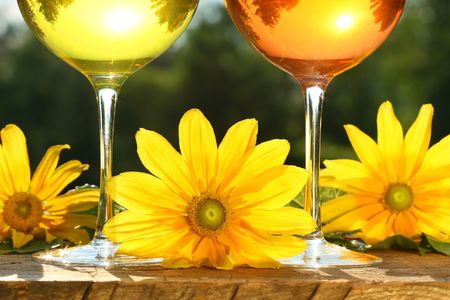 Golden wine in the sun on rustic table photo
