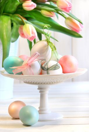 Colored eggs with bows and tulips for Easter photo