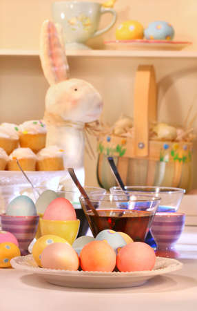 Dying eggs for Easter with cupcakes in background photo