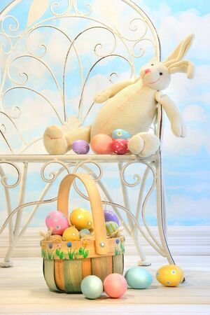 Easter bunny with eggs on garden chair photo