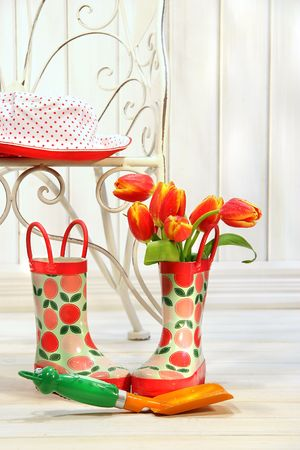 Iron chair with little rain boots and tulips beside Stock Photo - 2533398