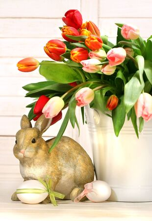 eastertime: Little rabbit behind white container full of tulips Stock Photo