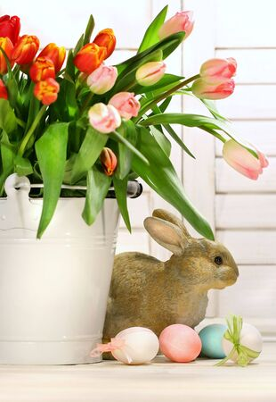 Pot of tulips with rabbit on the counter photo