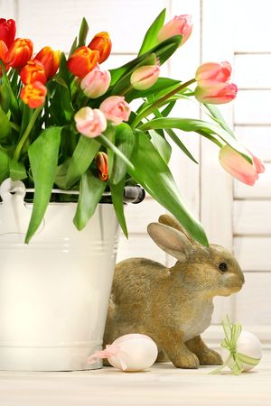 Rabbit hiding behind a white container of spring tulips photo