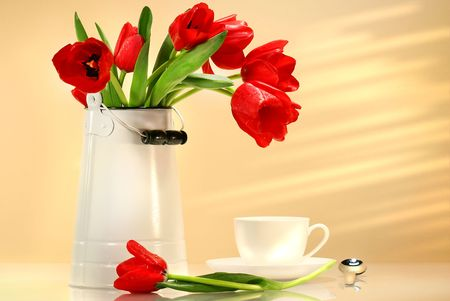 Red tulips in white container with tea cup photo