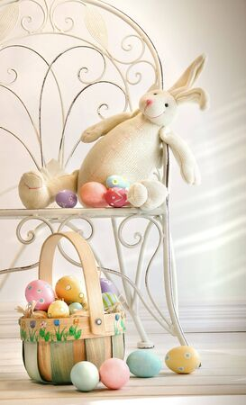Stuffed rabbit on iron chair with easter basket and eggs photo
