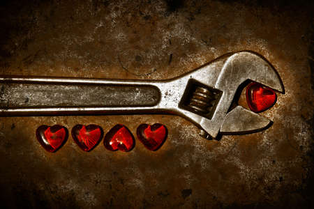 Five grunge hearts with wrench on rusty background Stock Photo