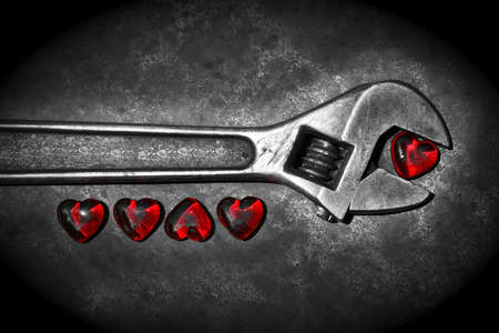 Five grunge hearts with wrench on rusty background BW