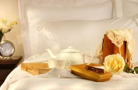 Tea in bed with chocolates and white sheets photo