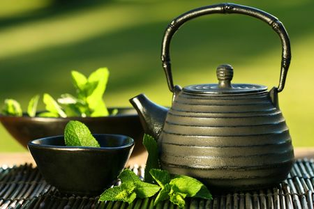 máta: Black iron asian teapot with sprigs of mint for tea