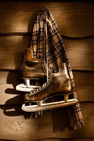 Oud hockey skates met sjaal opknoping op een muur  sepiatoon filter