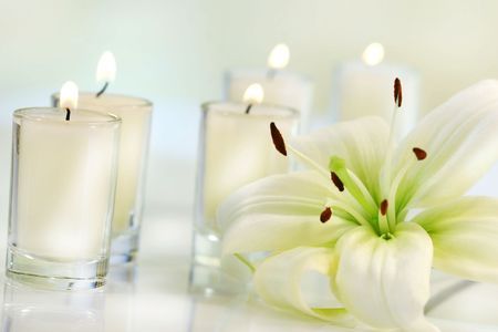 bath essence: Lily flower with candle on pale background Stock Photo