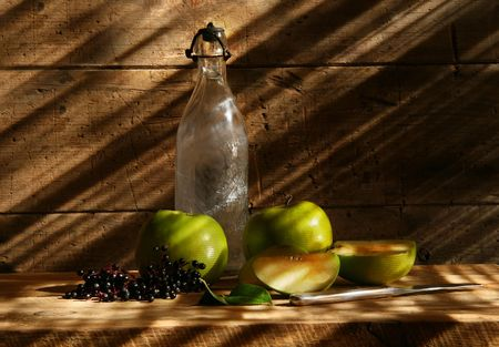 Old bottle and green apples with wood background photo