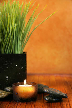 Spa setting with candle, stones and herb grass