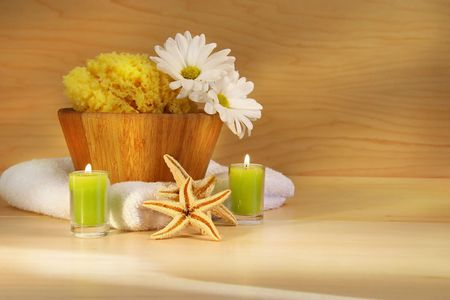 Wooden bowl, sponge, towel and candles on wooden counter