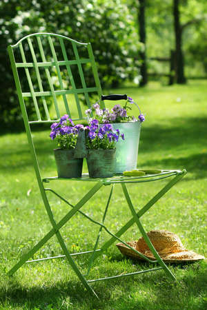 Green garden chair with straw hat Stock Photo