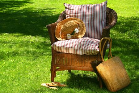 Straw hat and old wicker chair on the grass