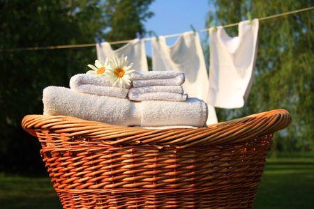 Rieten mand met wasgoed tegen een blauwe hemel-namiddag Stockfoto