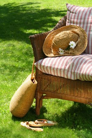 Grass lawn with a wicker chair waiting for someone to relax on a hot summers day Stock Photo