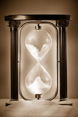 Hourglass resting on beach sand showing sand falling through glass photo