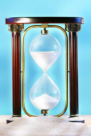 slow lane: Hourglass resting on beach sand showing sand falling through glass