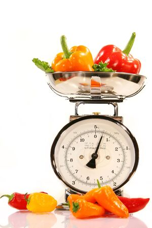 weighing: Colored peppers with kitchen food scale on white background