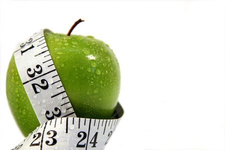 Measurement tape wrapped around green appleConcept for health, diet