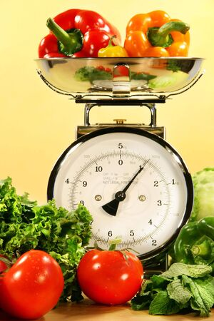 Fresh veggies on kitchen scale with yellow background photo