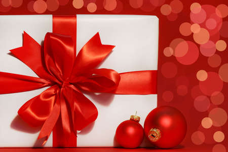 Big red bow on gift with red background and christmas balls Stock Photo